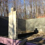 Pool house foundation built into side of hill.