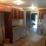Installation of cabinets begins in farmhouse kitchen.