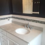 A custom vanity with Stilestone countertop provides practical, maintenance-free beauty and storage.